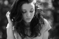 Nahaufnahme-Schwarzweiss-Porträt des attraktiven dunkelhaarigen Mädchens draußen Stockfotografie