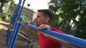 Nahaufnahme - sportlicher Mann, den das Handeln drückt, Ups Übung Turnhalle in der im Freien stock video