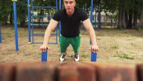Nahaufnahme - sportlicher Mann, den das Handeln drückt, Ups Übung Turnhalle in der im Freien stock footage