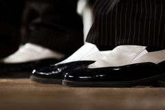 Nahaufnahme Stilvolle Schwarzweiss-Schuhe, zum am Stadium an den Füßen Männern durchzuführen lizenzfreie stockfotos