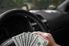 Nahaufnahme von amerikanischen Dollar auf einem Rad Bemannen Sie ` s Hand mit Geld auf einem schwarzen Autohintergrund Getrennte  Lizenzfreies Stockbild