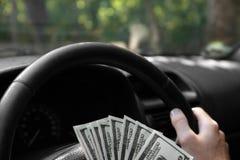 Nahaufnahme von amerikanischen Dollar auf einem Rad Bemannen Sie ` s Hand mit Geld auf einem schwarzen Autohintergrund Getrennte  Lizenzfreie Stockfotos
