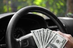 Nahaufnahme von amerikanischen Dollar auf einem Rad Ein Mann, der mit Geld auf einem Autohintergrund fährt Investitions- und Eins Lizenzfreies Stockbild
