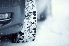 Nahaufnahme von Autoreifen auf einer schneebedeckten Straße Blizzard auf der Straße Stockfotos