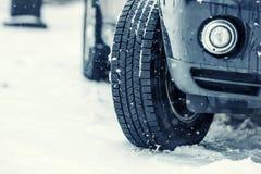 Nahaufnahme von Autoreifen auf einer schneebedeckten Straße Blizzard auf der Straße Lizenzfreie Stockfotografie