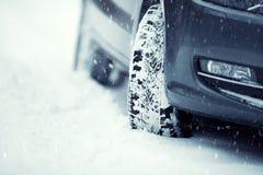 Nahaufnahme von Autoreifen auf einer schneebedeckten Straße Blizzard auf der Straße Lizenzfreie Stockfotos