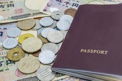 Nahaufnahme von Banknoten der japanischen Yen und japanische Yen prägen mit Pass Finanzgeld- und Reisekonzept Lizenzfreie Stockfotos
