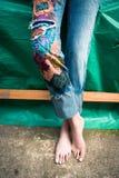 Nahaufnahme von barfüßigbeinen der jungen Frau in den boho Artjeans mit Co lizenzfreie stockbilder
