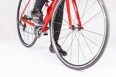 Nahaufnahme von Beinen des weiblichen Radfahrers und der Räder des Rennrads gelegt in Studio Lizenzfreie Stockfotos