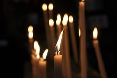 Nahaufnahme von brennenden Kerzen in einer Kirche Stockbilder
