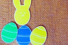 Nahaufnahme von bunten Papierkaninchen und von Papier ärgert Schattenbildrahmen gegen Segeltuchhintergrund Stockfotografie