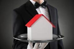 Nahaufnahme von Butler With House Model Stockbild