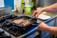 Nahaufnahme von Chef ` s Händen beim Backen des Fleisches lizenzfreie stockbilder