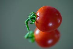 Nahaufnahme von Cherry Tomato auf Spiegel Lizenzfreies Stockfoto