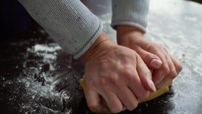 Nahaufnahme von den Frauenhänden, die rohen Teig auf der Tabelle bedeckt mit Mehl kneten stock video