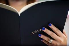 Nahaufnahme von den Frauenhänden, die Menü halten Stockfotos