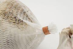 Nahaufnahme von den getrockneten Knoblauchknollen gezeigt mit dem Weiß, Plastikfiletarbeit, in der sie herein verkauft werden Stockfotos