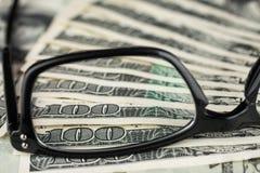 Nahaufnahme von den Gläsern, die auf dem Dollar liegen Stockfotografie