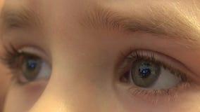Nahaufnahme von den glücklichen Baby-Augen, die Fernsehen, Reflexionen in den Augen schauen 4K UltraHD, UHD stock video footage