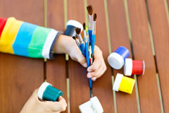 Nahaufnahme von den Händen des Kindes Aquarelle und Bürsten halten Stockbilder