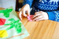 Nahaufnahme von den Händen des Kleinkindes Tulpe machend blüht Origami für eine Postkarte für Mutter ` s Tag oder Geburtstag Stockfotografie