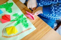 Nahaufnahme von den Händen des Kleinkindes Tulpe machend blüht Origami für eine Postkarte für Mutter ` s Tag oder Geburtstag Stockfoto