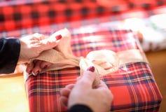 Nahaufnahme von den Händen, die Bogen auf Weihnachtsgeschenk binden stockbilder