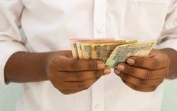 Nahaufnahme von den Händen, die indische Banknoten zählen stockfotografie