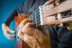 Nahaufnahme von den Händen und von Fingern eines Mannes, die klassisches gutar spielen Lizenzfreies Stockfoto