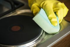 Nahaufnahme von den Händen, welche die Handschuhe abwischen den Ofen tragen Stockfotografie