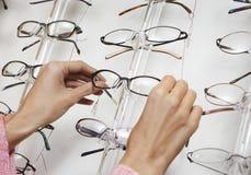 Nahaufnahme von den Händen, die Gläser vom Präsentationsständer ziehen Lizenzfreie Stockbilder