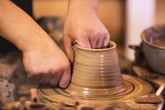 Nahaufnahme von den Händen, die Tonwaren auf einem Rad machen Lizenzfreie Stockbilder