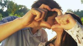 Nahaufnahme von den jungen Paaren, die ein Herz machen, formen am Sonnenuntergang und am Küssen stock video