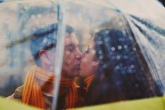 Nahaufnahme von den jungen schönen Paaren, die unter Regenschirm küssen Lizenzfreies Stockfoto