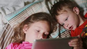 Nahaufnahme von den Kindern, die Tablet-Computer beim auf einem Bett zusammen liegen verwenden Mädchen, das Tabletten-PC, aufpass stock footage
