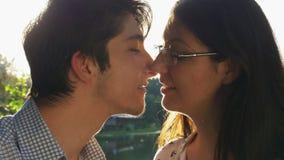 Nahaufnahme von den liebevollen Paaren, die bei Sonnenuntergang küssen stock footage