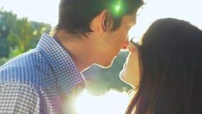 Nahaufnahme von den liebevollen Paaren, die bei Sonnenuntergang küssen und den Horizont untersuchen stock video