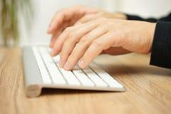 Nahaufnahme von den männlichen Händen, die auf Computertastatur schreiben Stockbilder