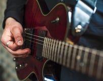 Nahaufnahme von den männlichen Händen, die auf E-Gitarre spielen Lizenzfreie Stockfotografie