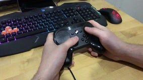 Nahaufnahme von den männlichen Händen, die einen Dampfprüfer vor dem hintergrund einer Spieltastatur und -maus mit einer Farbh stock video