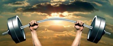 Nahaufnahme von den menschlichen Händen, die herauf Barbell über Himmel bei Sonnenaufgang anheben. Lizenzfreie Stockbilder
