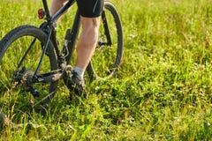 Nahaufnahme von den Radfahrermannbeinen, die Mountainbike auf die grüne Wiese reiten Stockfoto