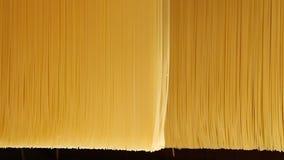 Nahaufnahme von den rohen Spaghettis, die in einer Teigwarenfabrik sich falten stock video footage