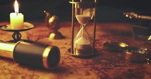 Nahaufnahme von den sandglass, die heraus auf Karte der Alten Welt im Kerzenlicht laufen stock video footage