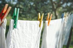 Nahaufnahme von den weißen T-Shirts, die auf einer Wäscheleine trocknen stockbilder