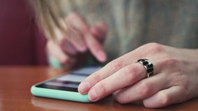 Nahaufnahme von den weiblichen Händen, die Text auf einem Smartphone angeschlossen an ein wifi Netz in einem Café schreiben stock footage