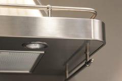 Nahaufnahme von Details von Knöpfen auf einem Metallabluftventilator mit Licht in einer Luxusküche lizenzfreies stockfoto
