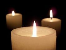 Nahaufnahme von drei beleuchtete Kerzen auf schwarzem Hintergrund. lizenzfreie stockfotografie