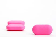 Nahaufnahme von drei rosafarbenen Pillen, getrennt Stockfotografie