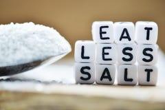 Nahaufnahme von Eat weniger Salztext geschrieben mit Plastikbuchstaben nahe einem Salzlöffel stockfotos